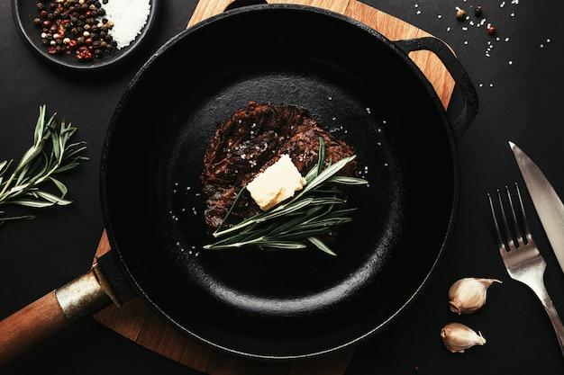 Ribeye-steak auf gusseiserner pfanne, pfeffer, rosmarin, knoblauch, messer, gabel, butter
