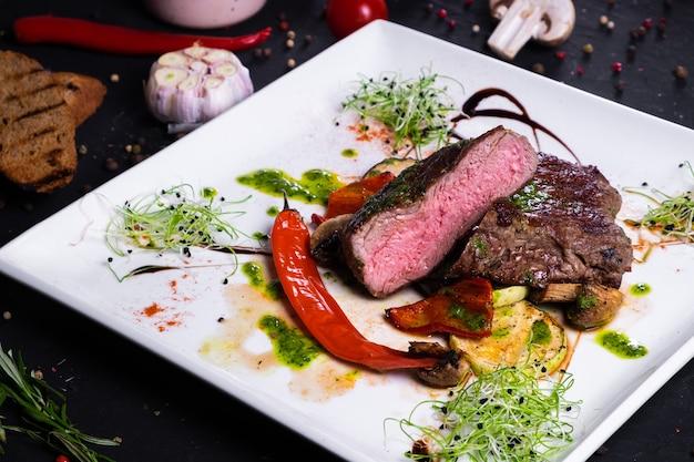 Ribeye-steak mit gegrilltem gemüse auf einem weißen teller auf dunkler oberfläche