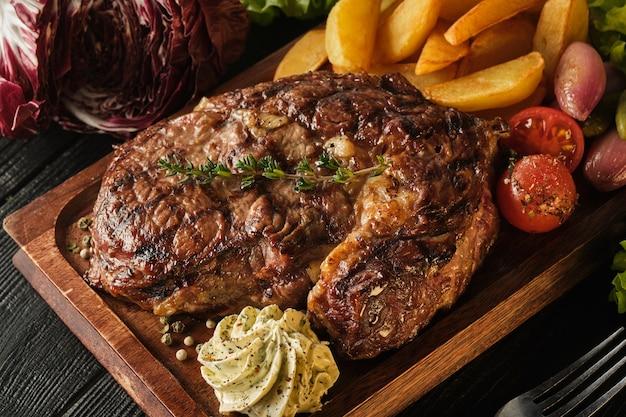 Ribeye steak mit kartoffeln, zwiebeln und gebackenen kirschtomaten