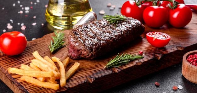 Ribeye-steak mit kartoffeln, zwiebeln und kirschtomaten. saftiges steak mit aromatisierter butter