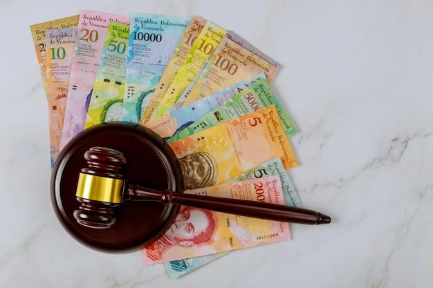 Richter am arbeitsplatz mit einer reihe von banknoten mit verschiedenen papierrechnungen währung venezuelan bolivar, venezuela wirtschaftsrichter hammergesetz