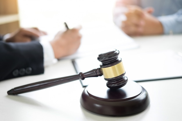 Richter hammer mit anwälten beratung rechtsanwalt im hintergrund. konzepte des rechts, dienstleistungen