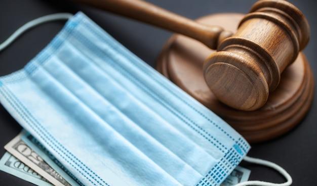Richter hammer mit medizinischer maske und geld auf dunklem hintergrund korruption im medizinischen feldkonzept
