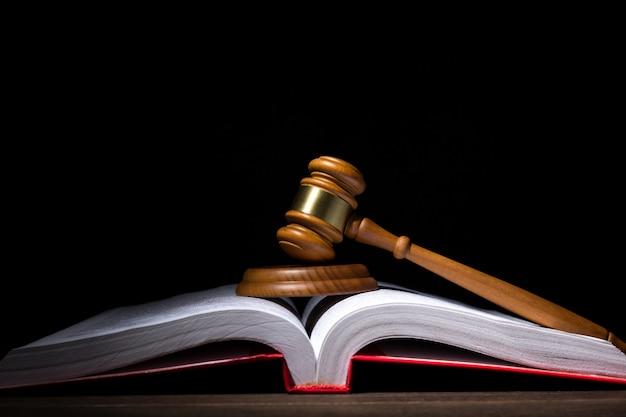 Richter hammer mit resonanzboden auf großem geöffnetem gesetzbuch gegen schwarzen hintergrund.