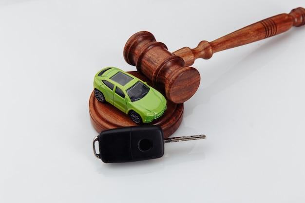 Richter hammer und grünes spielzeugauto mit schlüsseln auf weißer wand. symbol für recht, gerechtigkeit und autoauktion
