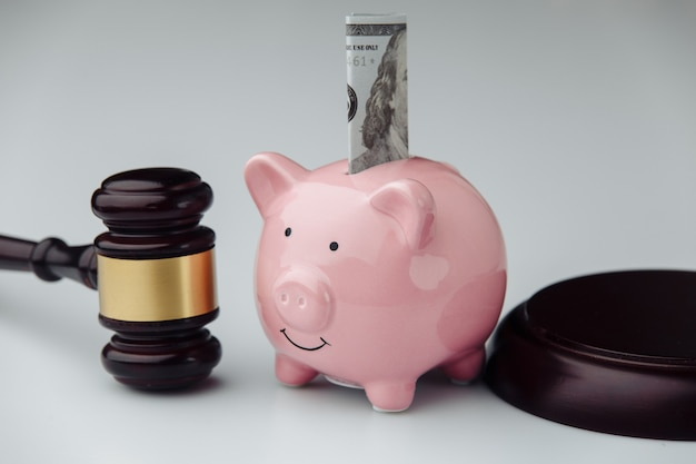 Richter hammer und rosa sparschwein mit dollarschein. kredit- und finanzkonzept.