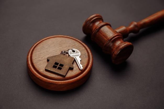 Richter hammer und schlüsselanhänger in form von zwei geteilten teilen des hauses auf holz.