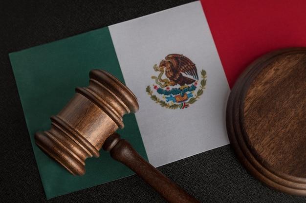 Richter oder auktionshammer auf flagge von mexiko. mexikanische gesetzgebung. verletzung der menschenrechte in mexiko