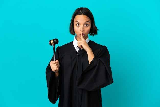 Richter über isolierten blauen hintergrund, der ein zeichen der stille zeigt, geste, die finger in den mund steckt Premium Fotos