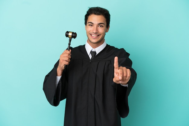 Richter über isolierten blauen hintergrund, der einen finger zeigt und anhebt