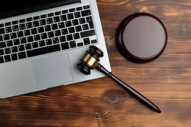 Richterhammer auf einem laptop mit einem hölzernen hintergrund und einer draufsicht.