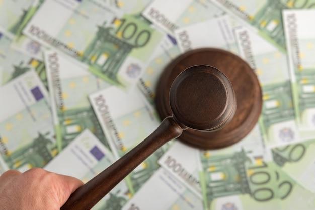 Richterhammer auf eurobanknotenhintergrund. richterhammer auf dem geld. korruptes gericht.