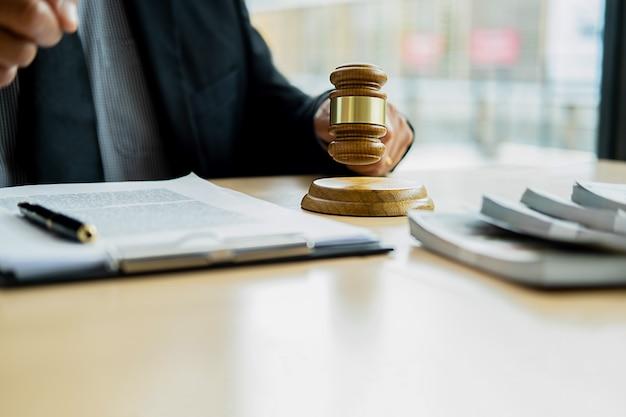 Richterhammer mit dem gerechtigkeitsanwalt, der teambesprechung in der anwaltskanzlei hat