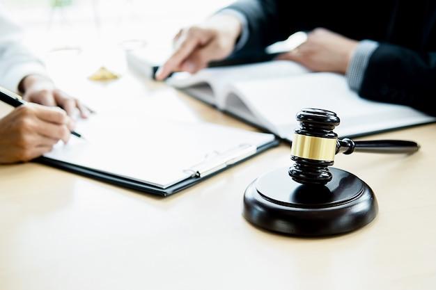 Richterhammer mit dem gerechtigkeitsanwalt, der teamsitzung in der anwaltskanzlei mit kanzleihintergrund hat.