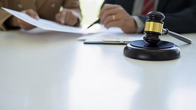 Richterhammer mit den gerechtigkeitsanwälten, die teambesprechung in der anwaltskanzlei haben.