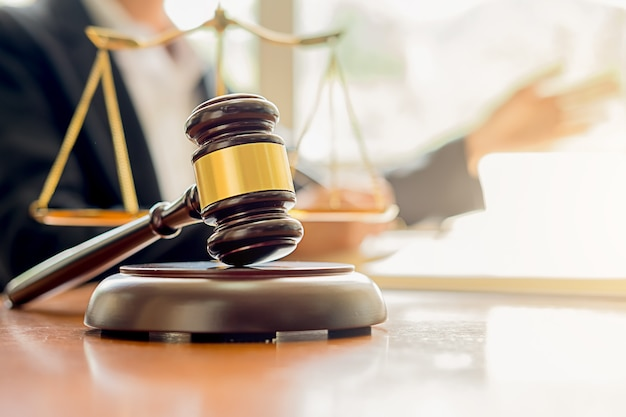 Richterhammer mit den justizanwälten, die teamtreffen am anwaltskanzleihintergrund haben.