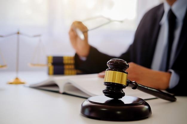 Richterhammer mit den justizanwälten, die teamtreffen an der anwaltskanzlei im hintergrund haben.