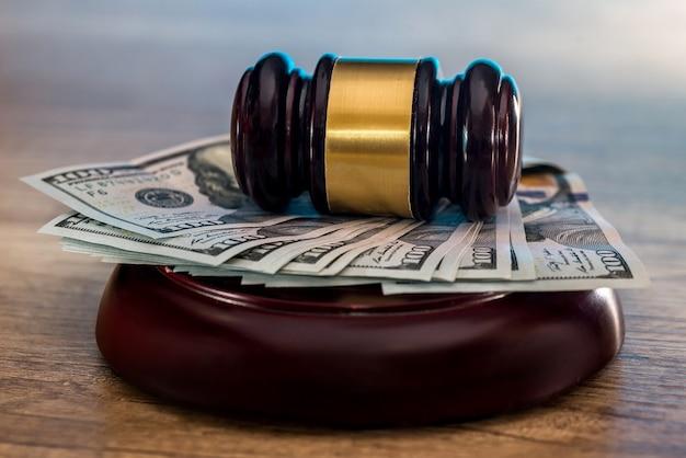 Richterhammer mit dollar in rolle und goldenen münzen