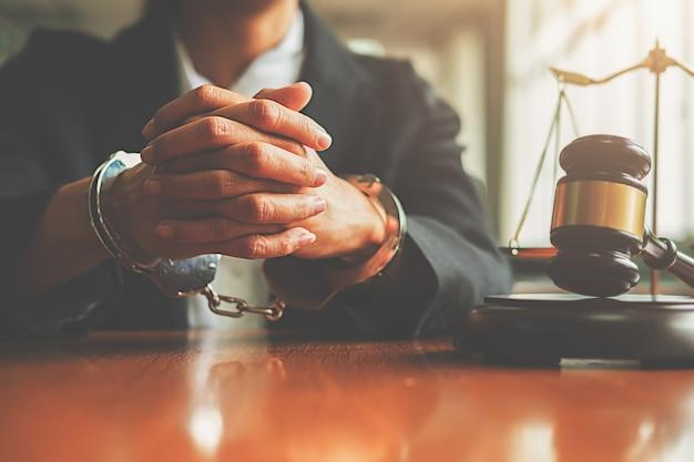 Richterhammer mit gerechtigkeitsrechtsanwalt in den handschellen, die sich traurig und betonen fühlen.