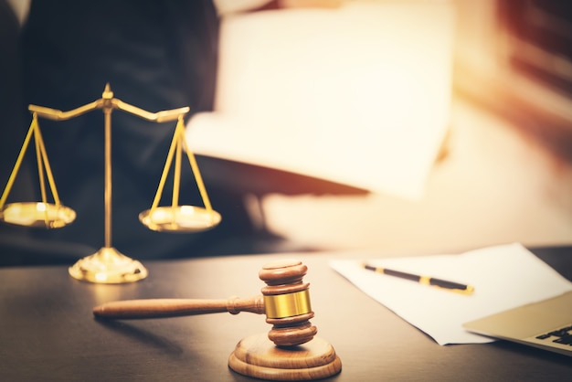 Richterhammer mit gesetzesbuch auf holztisch und skaliert gerechtigkeit, anwaltskonzept