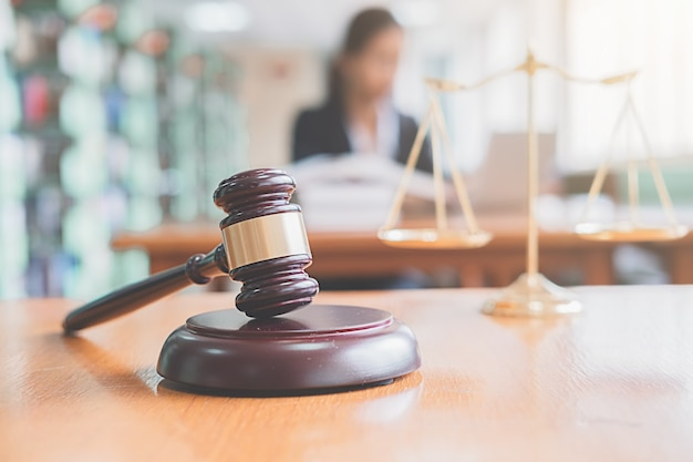 Richterhammer mit justizanwälten, die teambesprechung am hintergrund der kanzlei haben. rechtsbegriffe und juristische dienstleistungen.