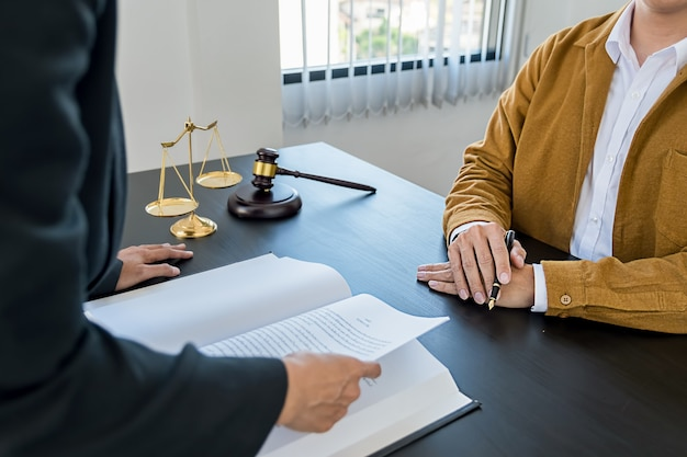 Richterhammer mit justizanwälten, die teamsitzungen im hintergrund der anwaltskanzlei haben. rechtsbegriffe und rechtsdienstleistungen.