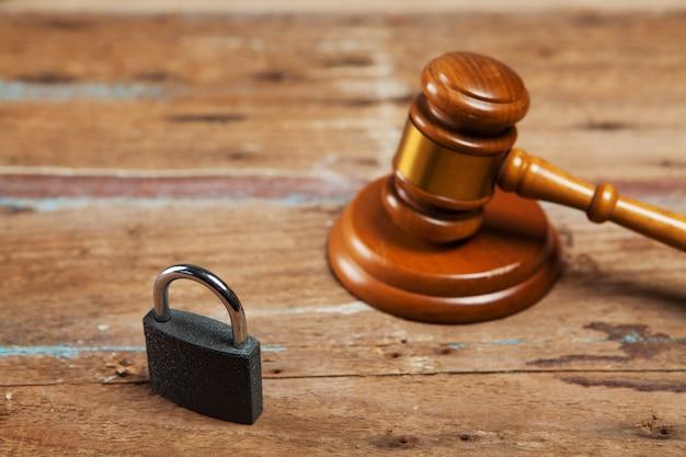 Richterhammer mit vorhängeschloss auf dem tisch. recht und sicherheitskonzept
