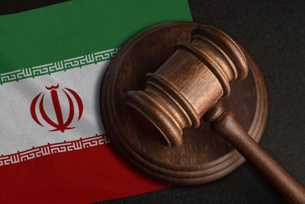 Richterhammer und flagge des iran. recht und gerechtigkeit im iran. verletzung von rechten und freiheiten.
