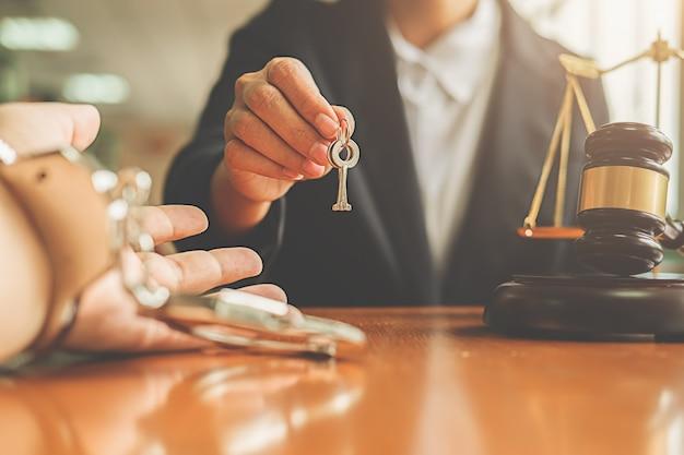 Richterhammer und gerechtigkeitsrechtsanwalt, die dem mann in den handschellen den schlüssel geben, der das gefühl traurig und betont.