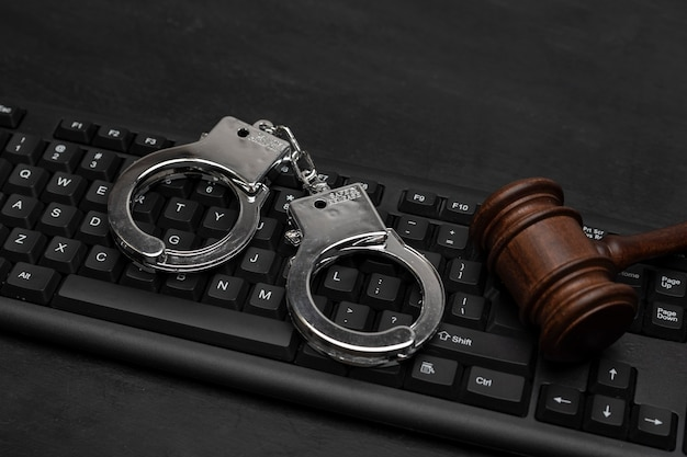Richterhammer und handschellen auf der computertastatur. cyberkriminalität. gesetzliche haftung im internet. online-piraterie.
