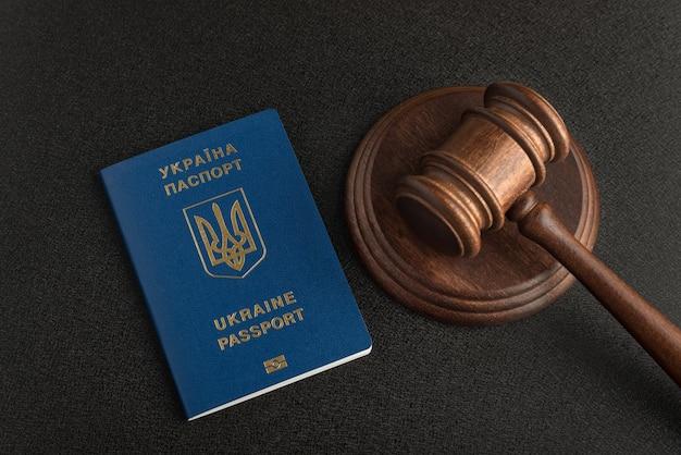 Richterhammer und reisepass eines bürgers der ukraine. schwarzer hintergrund. staatsbürgerschaft erlangen.
