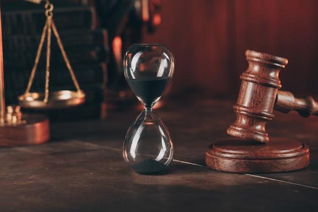 Richterhammer, waage der gerechtigkeit und sanduhr in einem gerichtssaal. konzept von recht und gerechtigkeit