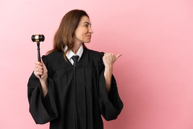 Richterin mittleren alters isoliert auf rosa hintergrund, die auf die seite zeigt, um ein produkt zu präsentieren