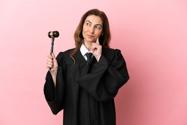 Richterin mittleren alters isoliert auf rosa hintergrund, die eine idee denkt, während sie nach oben schaut