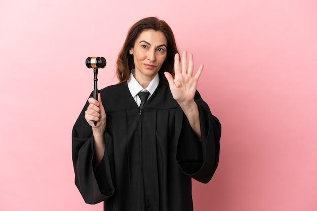 Richterin mittleren alters isoliert auf rosa hintergrund und zählt fünf mit den fingern