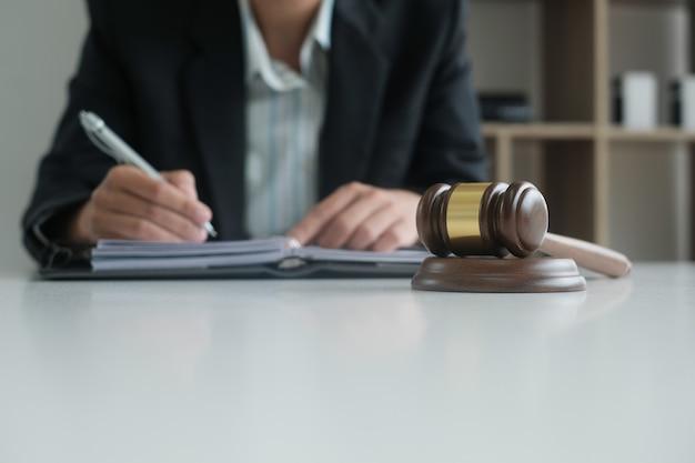Richterschreibensanmerkung mit gesetzeshammer auf schreibtisch.
