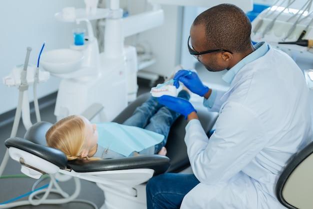 Richtiger algorithmus. professioneller männlicher zahnarzt, der ein zahnmodell hält und eine zahnbürste verwendet, während er seinem kleinen patienten zeigt, wie man zähne richtig putzt