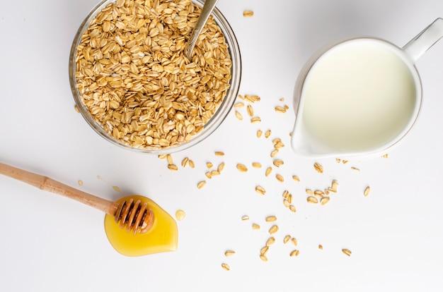 Richtiges ernährungsmenü zum frühstück mit haferflocken, milchglas und honigschöpflöffel