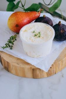 Ricotta-käse mit pfirsich, feigen und thymian auf holzbrett