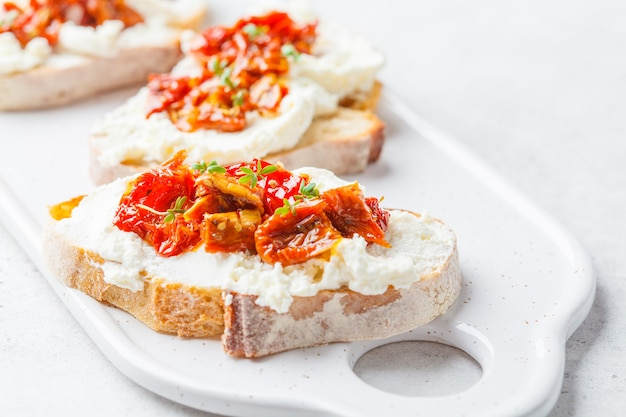 Ricotta und sonnengetrocknete tomatensandwiche auf weißem brett.