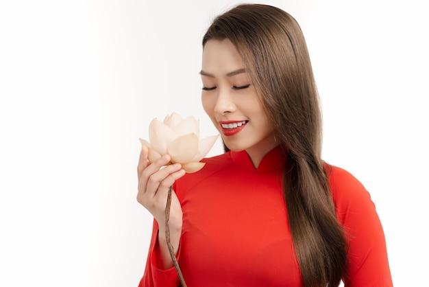 Riechende blume der eleganten asiatin und das tragen von ao dai auf weiß.