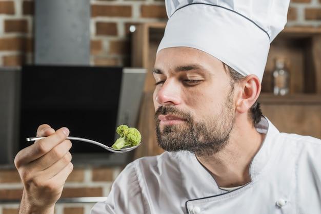Riechender brokkoli des männlichen chefs im edelstahllöffel