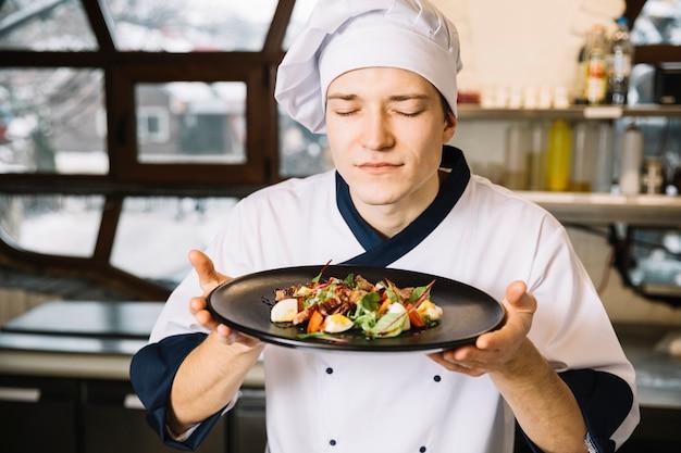 Riechender salat des kochs mit fleisch auf platte