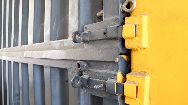 Riegel und verschluss einer standardmäßigen gelben und grauen metallischen seefrachtcontainernahaufnahme.