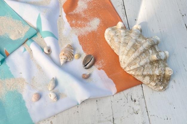 Riesenmuschel und andere muscheln auf einem strandtuch auf weißem brett