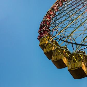 Riesenrad des niedrigen winkels mit blauem himmel