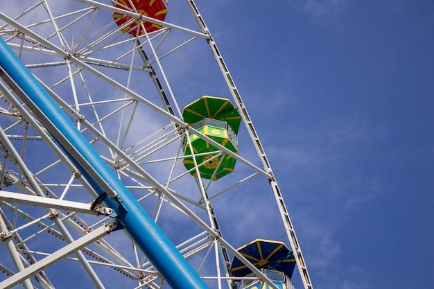 Riesenrad gegen den himmel. bunte stände des riesenrades. untersicht.