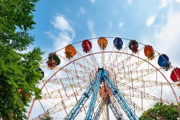Riesenrad im grünen park über blauem himmel mit wolken