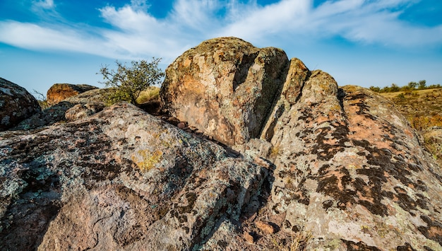 Riesige ablagerungen alter steinmineralien, die mit vegetation bedeckt sind, auf einer wiese voller warmer sonne in der ukraine und ihrer wunderschönen natur