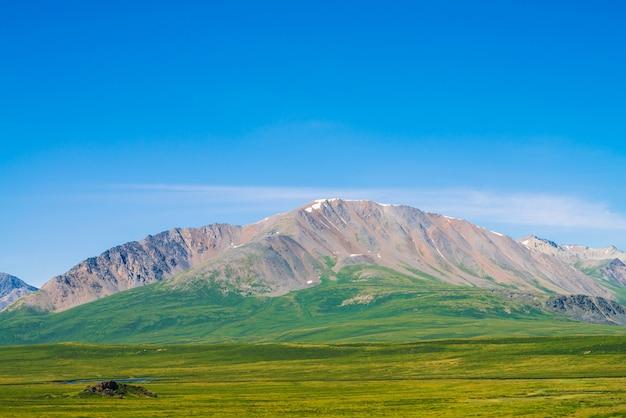 Riesige berge mit schnee über grünem tal unter klarem blauem himmel. wiese mit reicher vegetation und hochlandseen im sonnenlicht. erstaunliche sonnige berglandschaft der majestätischen natur.